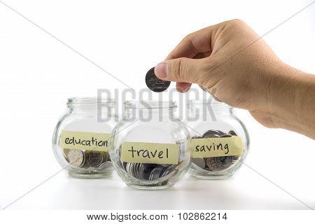 Hand Putting Coin Into Glass Container With Saving, Education And Travel Label On White Background.