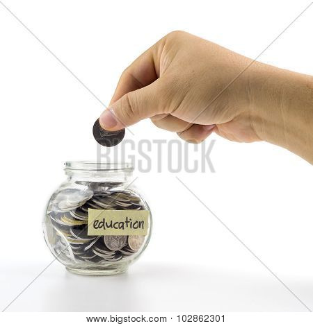 Hand Putting Coin Into Glass Container With  Education Label On White Background. Selective Focus.