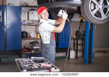 Mechanic Screwing A Tyre
