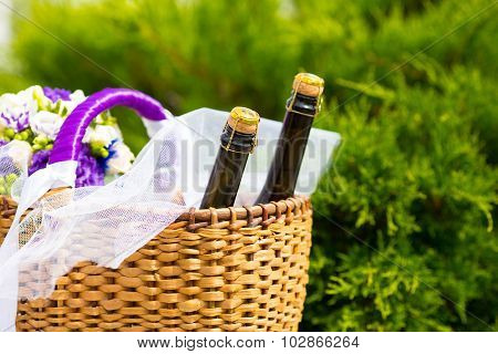 Wicker basket with two bottles champaign and flowers