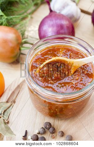 Homemade tomato sauce in glass jar with fresh tomatos, garlic, onion, herbs and spices
