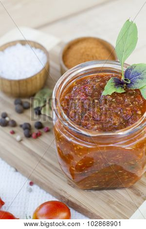Homemade tomato sauce in glass jar with fresh tomatos, garlic, onion, herbs and spices, close up