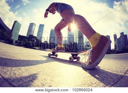 skateboarding legs riding on skateboard at sunrise city