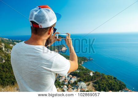 Man Makes Photos By A Smartphone On The Background Of Sea Coast, Adriatic Sea, Montenegro