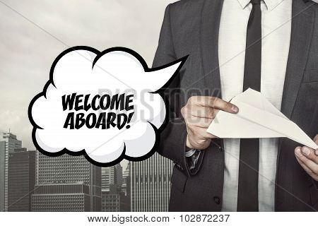 Welcome aboard text on speech bubble with businessman holding paper plane in hand