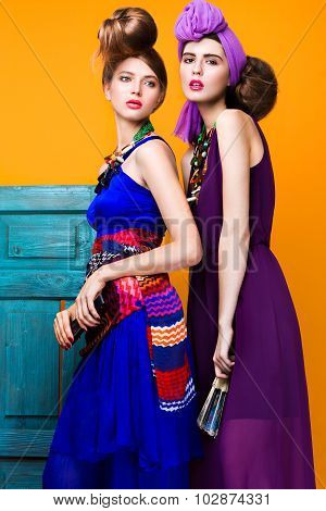 Beautiful fashionable women an unusual hairstyle in bright clothes and colorful accessories.