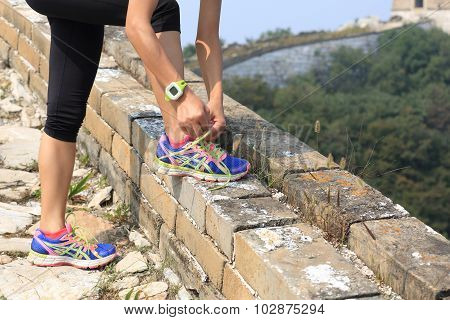 woman runner tying shoelace on china great wall.