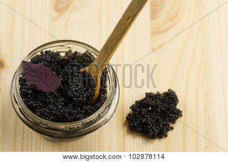 Black Beluga Caviar In Glass Jar On Wooden Background