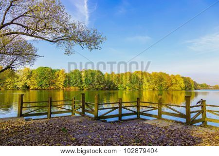 View From Pier On Lake And Colourful Trees In The Public Park In Autumn Time