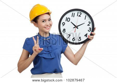 Asian Engineer Woman Show Victory Sign With A Clock