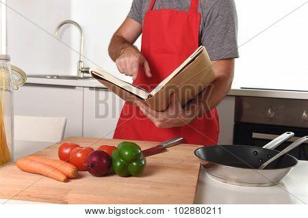 Unrecognizable Man In Apron At Kitchen Following Recipe Book Hea