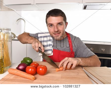 Young Home Cook Man In Apron Slicing Carrot With Kitchen Knife Happy And Relaxed