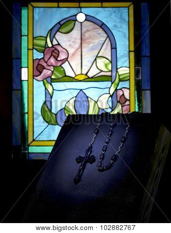 Vintage Rosary On Book With Stained Glass Evening Light
