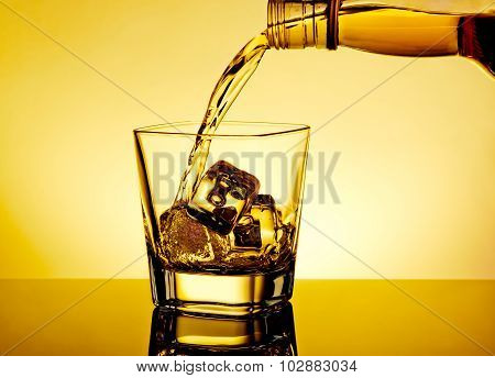 Barman Pouring Whiskey In The Glass On Table With Reflection, Warm Tint Atmosphere