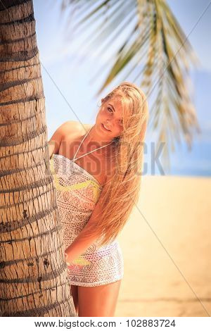 Blonde Girl In Lace Closeup Leans Out Of Palm Smiles On Beach