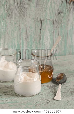 Greek Yogurt And Honey In A Glass Jar On Blue Wooden Surface, Vintage And Rustic Style