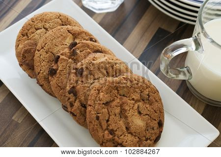 Chocolate Chip Cookies And Milk On Dark Wood Table