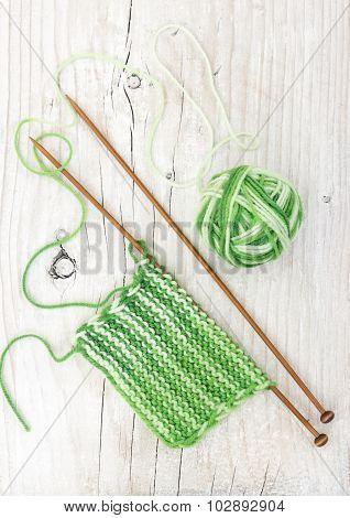 Knitting Pattern Of Green Yarn On Wooden Needles
