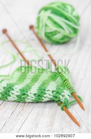 Knitting Pattern Of Green Yarn On Wooden Needles On A Wooden Background