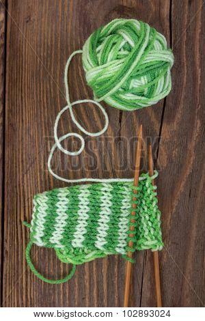 Knitting Pattern Of Green Yarn On A Wooden Background
