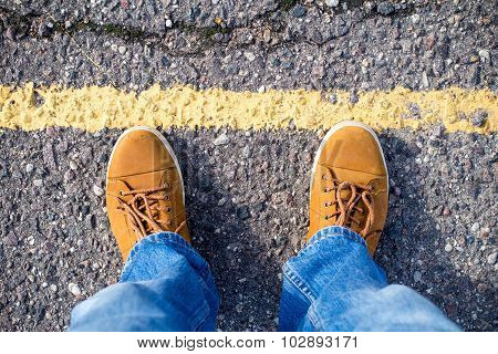 Top View Of Male Sneakers On The Asphalt Road