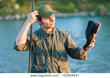 Disappointed fisher catching a shoe instead of a fish