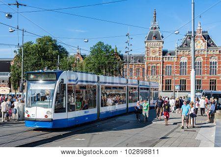Tourists Walking Near A Tram In Amsterdam