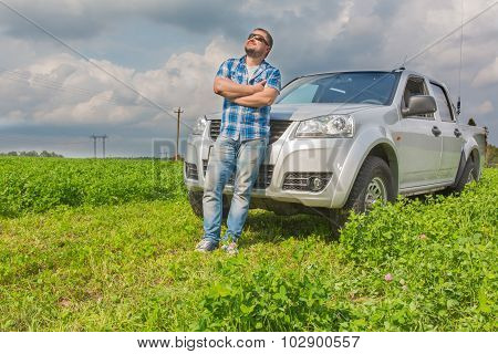 Man standing in front of car leaned on cowl and looking up in the sky