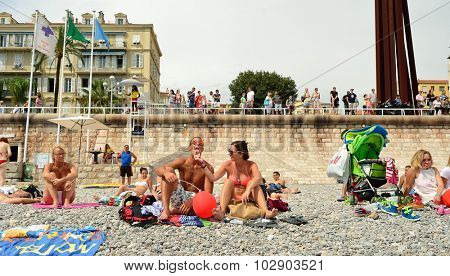 NICE, FRANCE - AUGUST 15, 2015: people on the beach. Nice is the fifth most populous city in France, after Paris, Marseille, Lyon and Toulouse, and it is the capital of the Alpes Maritimes departement