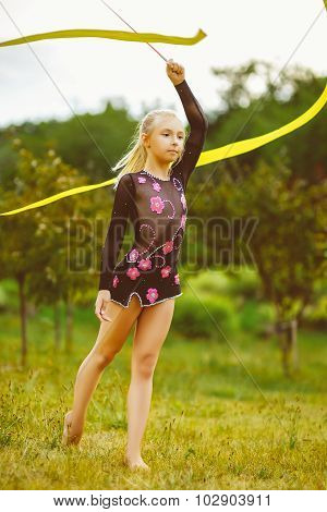 Young gymnast warms up with a gymnastic tape or feed. Warm toned photo