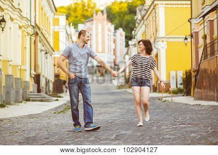 Happy couple in love walking at city. Warm toned photo