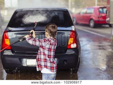child washing the car with a hose