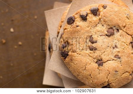 Stacked chocolate chip cookies on brown wooden table