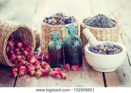 Bottles Of Tincture, Basket With Rose Buds, Lavender And Dried Forget Me Not Flowers In Mortar. Herb