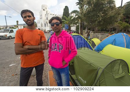 KOS, GREECE - SEP 27, 2015: Unidentified war refugees near tents. More than half are migrants from Syria, but there are refugees from other countries -Afghanistan, Pakistan, Iraq, Iran, Mali, Somalia.