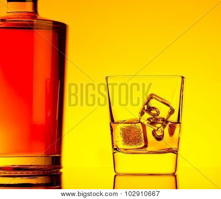 One Glass Of Whiskey With Ice Cubes Near Bottle On Table With Reflection, Warm Tint Atmosphere