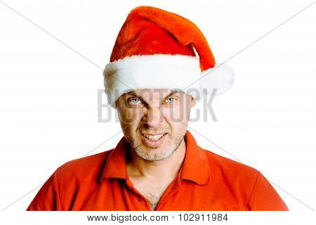 Unshaven Angry Man In A Red Shirt And Santa Hats. Studio. Isolated