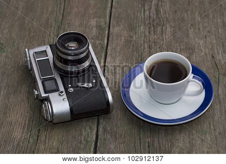 The Old Camera And Cup Of Coffee On A Wooden Table