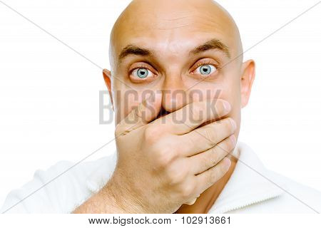 Bald Frightened Man In A White Jacket Covers Her Mouth With His Hand. Studio. Isolated