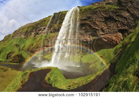 Summer sunny day. Large rainbow decorates a drop of water. Seljalandsfoss waterfall in Iceland. The picture was taken Fisheye lens