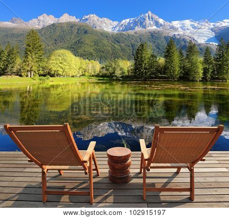Comfortable lounge chairs on wooden platform for rest and observation. City park in the Alpine resort of Chamonix
