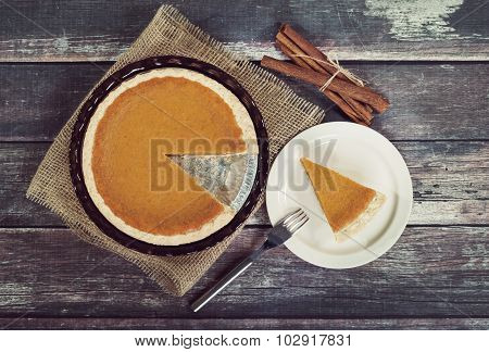 Pumpkin Pie With Cinnamon Sticks Against Rustic Wooden Table