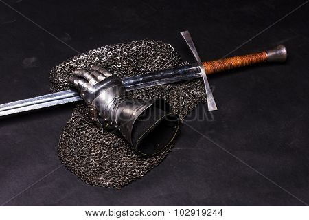 Medieval chain mail, iron gauntlet and a bastard sword still life on a dark background