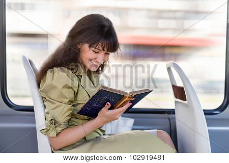 Happy Girl Reading In The Tram