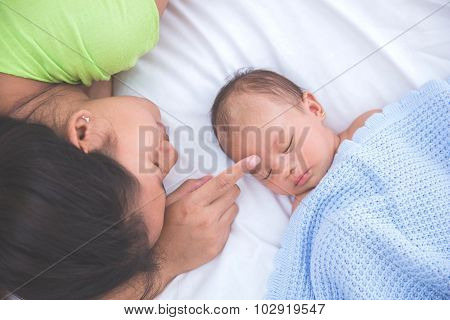 Baby Sleeping With Woman Touching Her Forehead