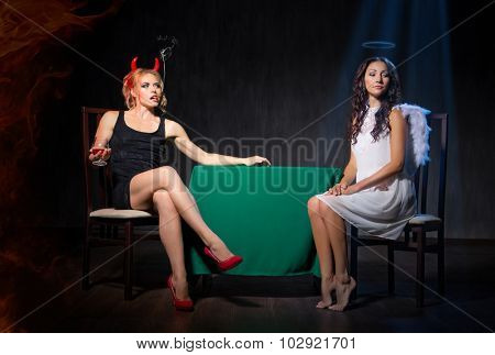 Angel and devil with cigar on dark background