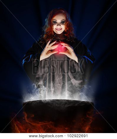 Young witch with potion and cauldron on blue rays background