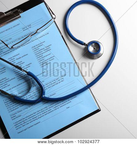 Stethoscope on medical history isolated on white