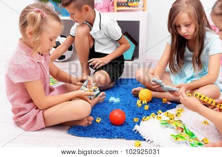 Group of children playing on floor in classroom
