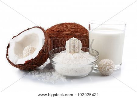 Candies in coconut flakes, glass of milk and fresh coconut isolated on white